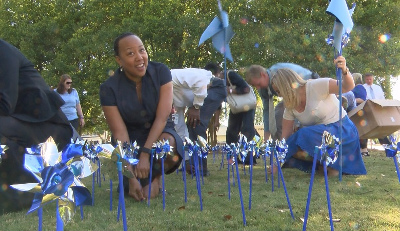 CASA coordinator Rosalind Alston plants a pinwheel to signify the number of reported cases of child abuse in Georgia.