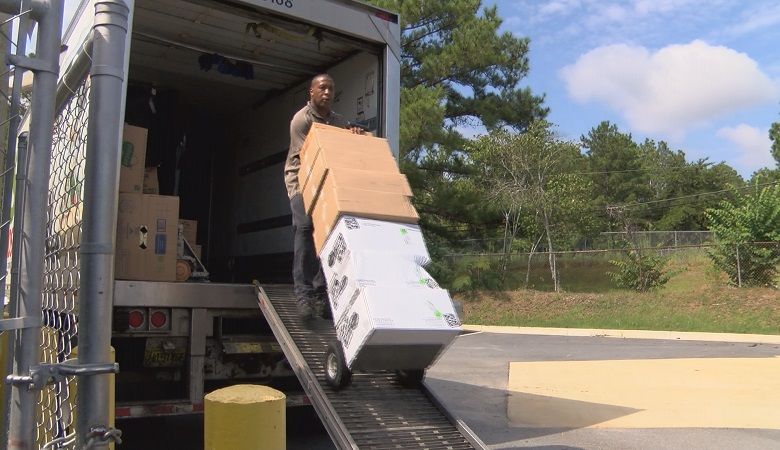 Deliverymen carry tons of food into school kitchens, preparing for the 2016-2017 school year in Muscogee County.