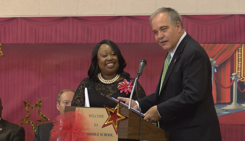 Georgia Schools Superintendent Richard Woods presents Fort Middle School Sonja Matthews-Coaxum with the family-friendly school award.
