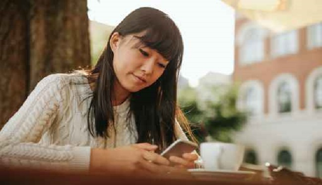 Young woman with a coffee using mobile phone_158173